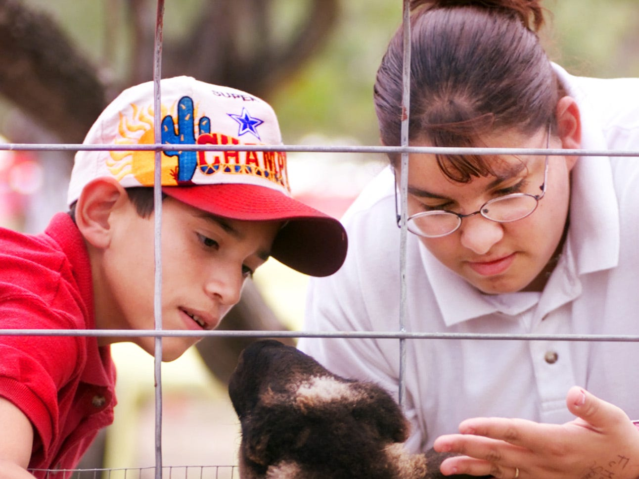 14-yr-old Chris Garcia (left), and his sister 15-yr-old Frances Garcia (right), with a sheep in the petting zoo inside Texas Sky Festival Park in October 2000.Both are students at West Oso High School.