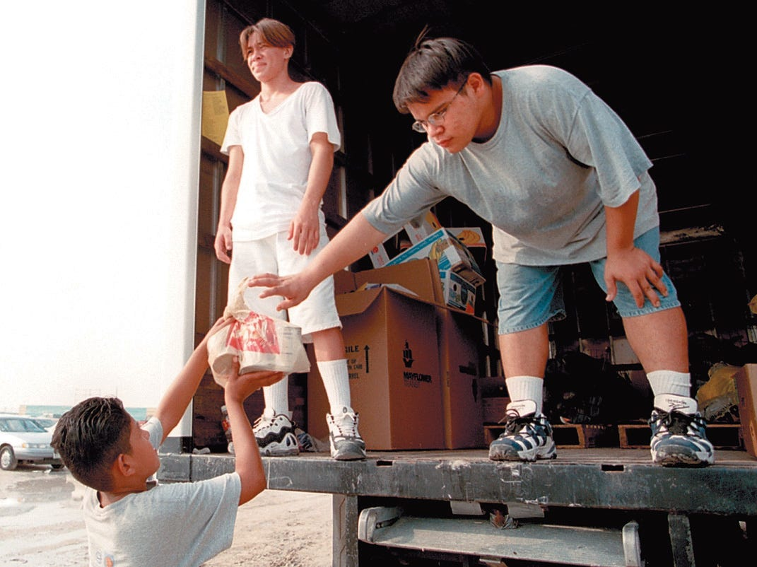 Richard Martinez,11, (left) hands Ricky Castillo,17, a bag of items donated by Freddie Fest 97 concert goers outside the gates at Texas Sky Festival Park Aug. 24, 1997. Admission was free for those who donated canned food or school supplies that will benefit local charities.