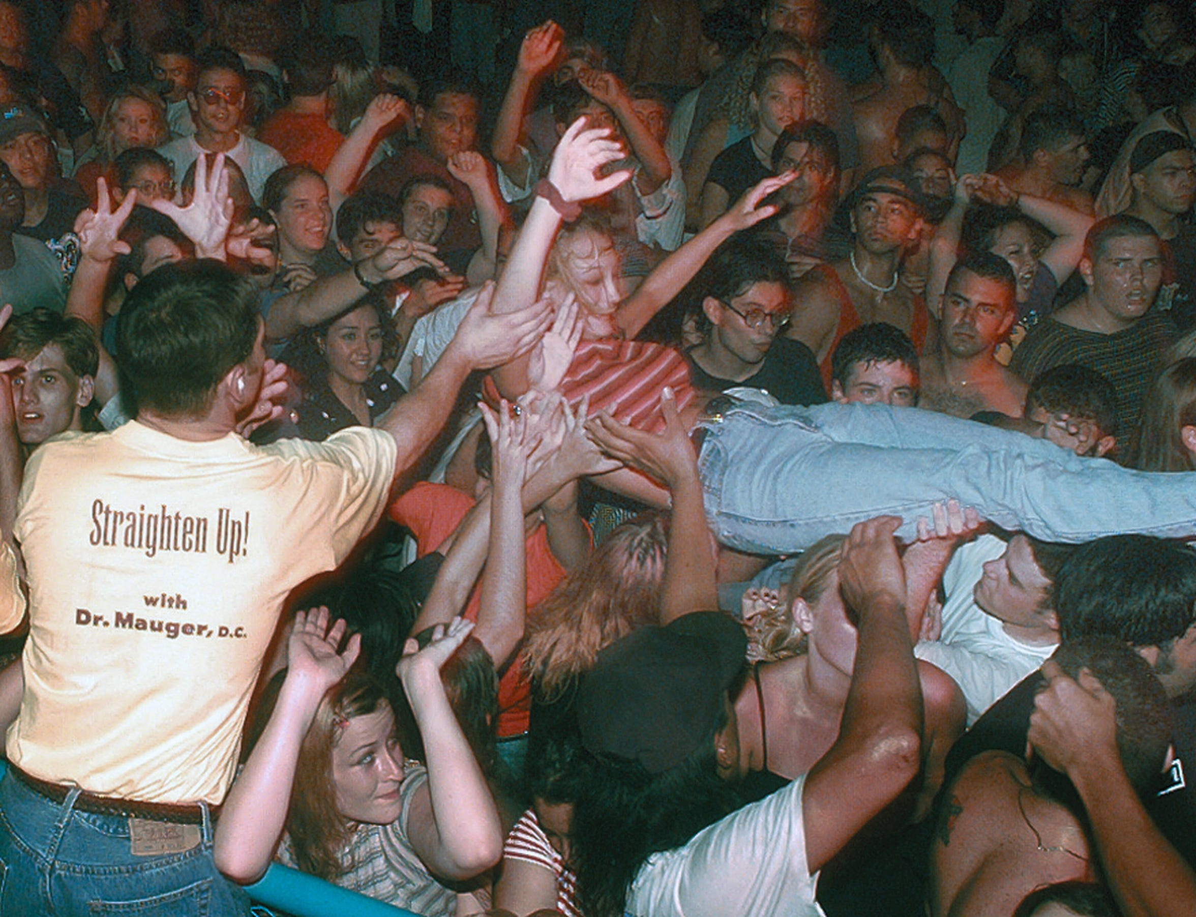 A concert goer is carried over the crowd toward a security guard at Texas Sky Festival Park in Corpus Christi during the Toadies concert on July 6, 1996.Photo by  7-6-96