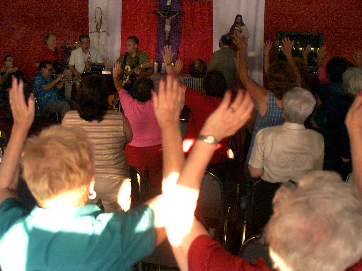 The audience raises their hands during a hymn at a revival meeting at Our Father's House, formerly the Texas Sky Festival Park, on Tuesday, June 25, 2002.