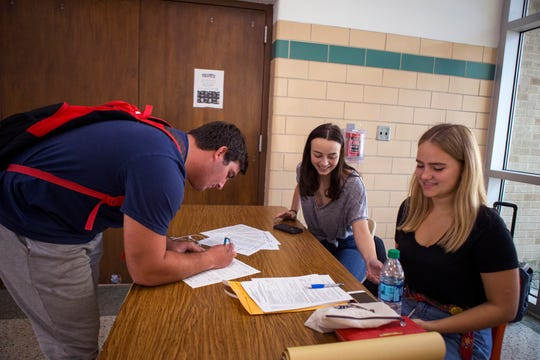 Ray High School student Thomas Holland (from left), 18, registers to vote with the help of students Isabel Ostos, 17, and Lillie Zuniga, 18, at the school on Wednesday, October 3, 2018.