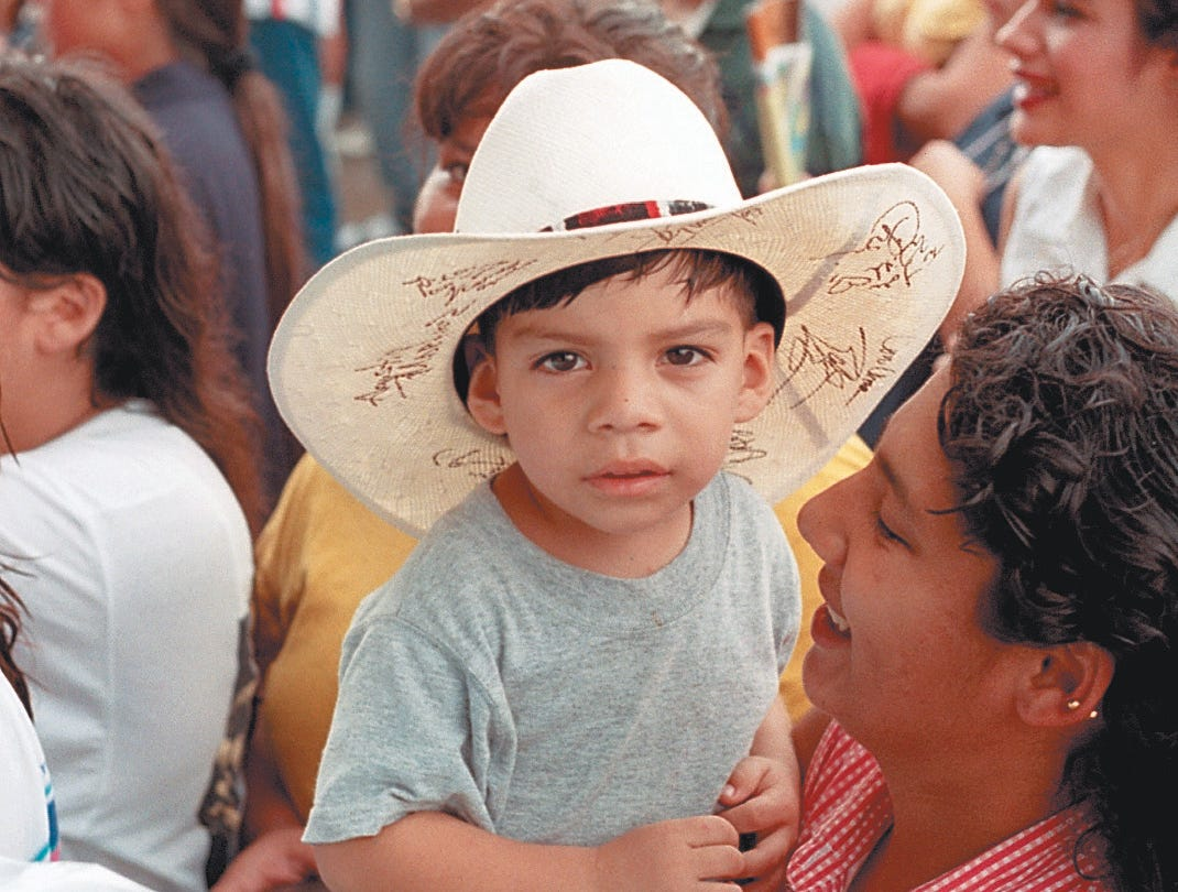 David Chapa Jr. gets front row with the help of his aunt Lorianne Morin, 19, (right) during the performance of Fandango USA at Freddie Fest 97 on Aug. 24, 1997 at Texas Sky Festival Park in Corpus Christi, TX.