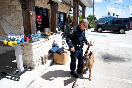 Corpus Christi Police dog handlers and their K9's stands outside the Southside Animal Hospital where they where presented with gifts on Wednesday, Oct. 3, 2018.