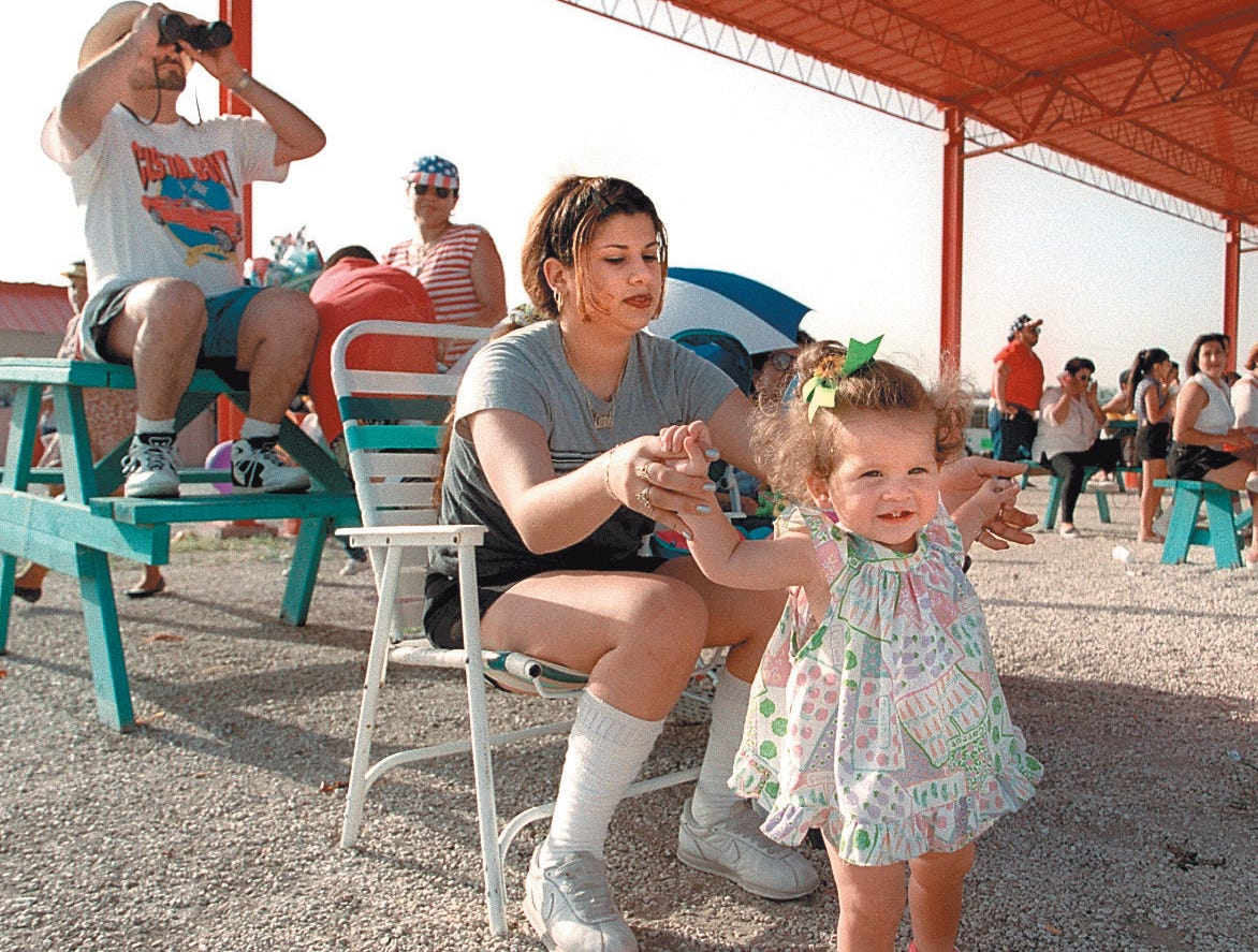 Lora Wilmot holds on to her daughter Zana Wilmot, 1, while Jaime y Los Chamacos perform at the Freedom Fest at Texas Sky Festival Park Juyl 3, 1997.
