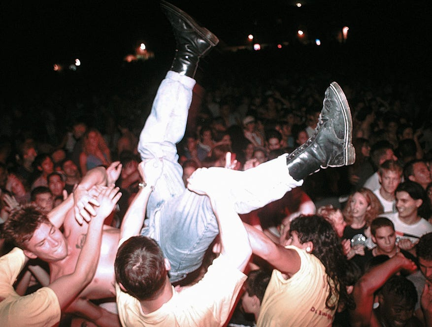A concert goer is grabbed by security guards at the barrier after being carried across the top of the crowd at Texas Sky Festival Park during the Toadies concert on July 6, 1996.