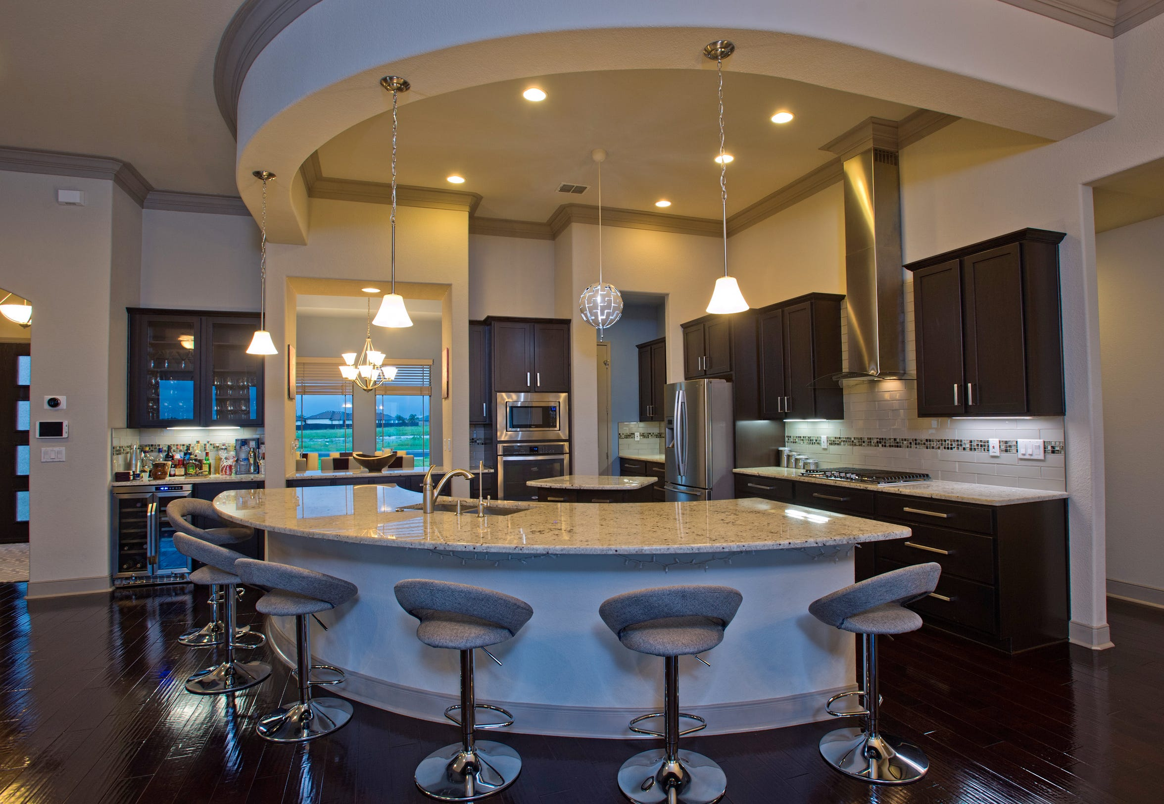 This gourmet kitchen and eating area must be experienced.  The area features expansive cabinetry, granite counters, glass backsplash and large curved center island with adjoining pantry and butler's pantry; all open to the living space.