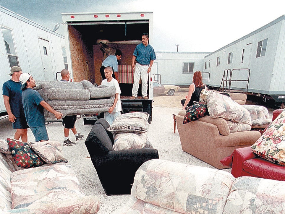 Employees from Action Home Choice of Corpus Christi and 462 Concerts work together on Aug. 1, 1997 to unload eight living rooms sets for the band trailers  performing at Lollapalooza Aug. 3, 1997 at Texas Sky Park.