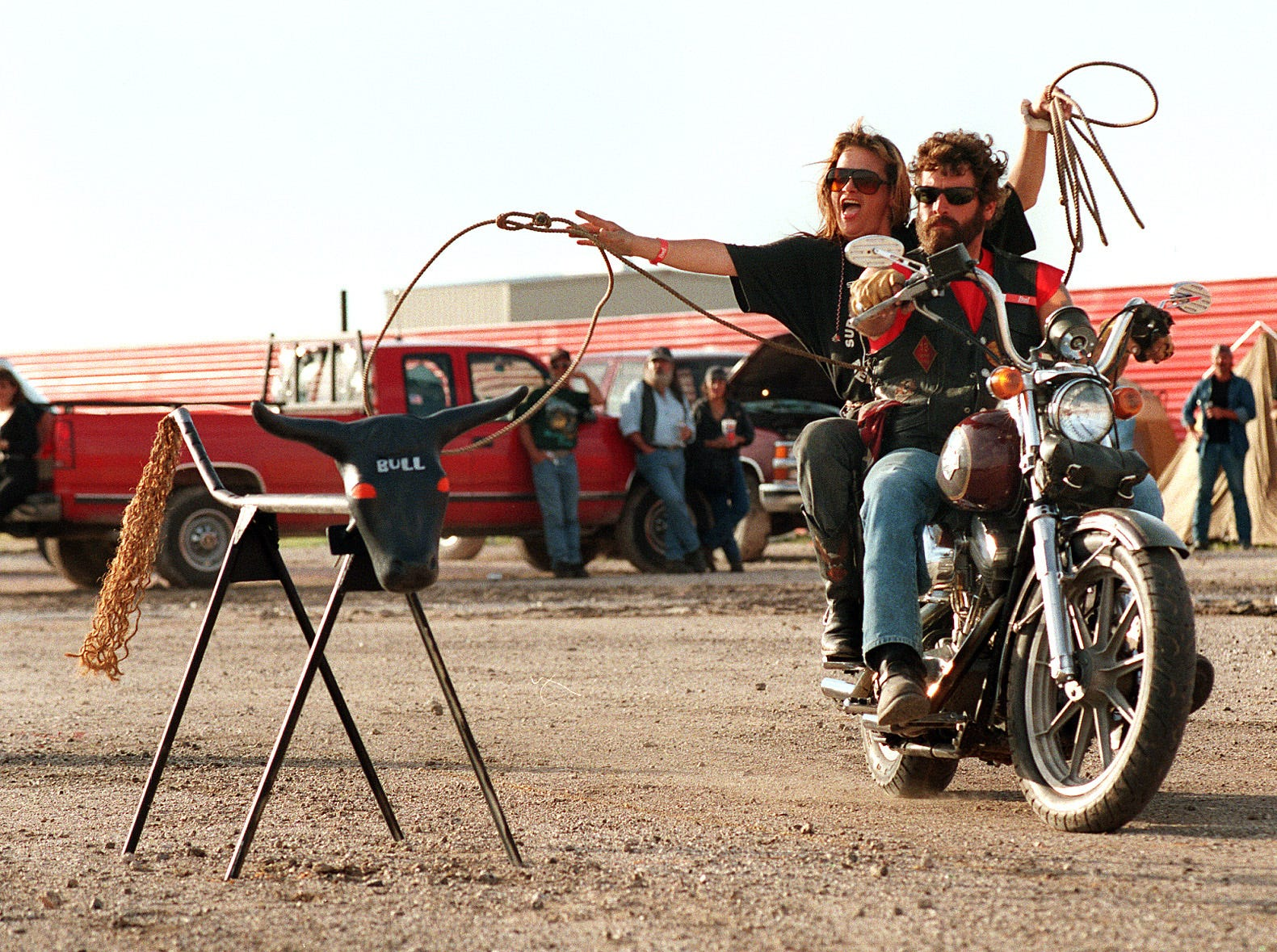"T.J. Jenkins tries her best to lasso a ""bull"" as driver Brent Kline moves them past their target during the motorcycle rodeo competition at the Second Annual Ride For Flight, a benefit for Halo Flight at Texas Sky Festival Park in Corpus Christi, TX on Sept. 28, 1996. The roping team was unable to rope the bull on the try."