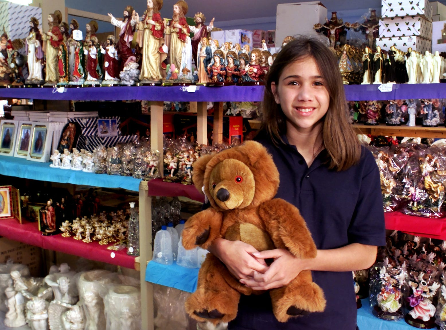 11-yr-old Ariana Camina holds a Bluebell Bear in St. Jude's House of Angels inside Texas Sky Festival Park on Jurica Road in October 2000. The bear recites a prayer and is one of many religious and spiritual items sold at the store.