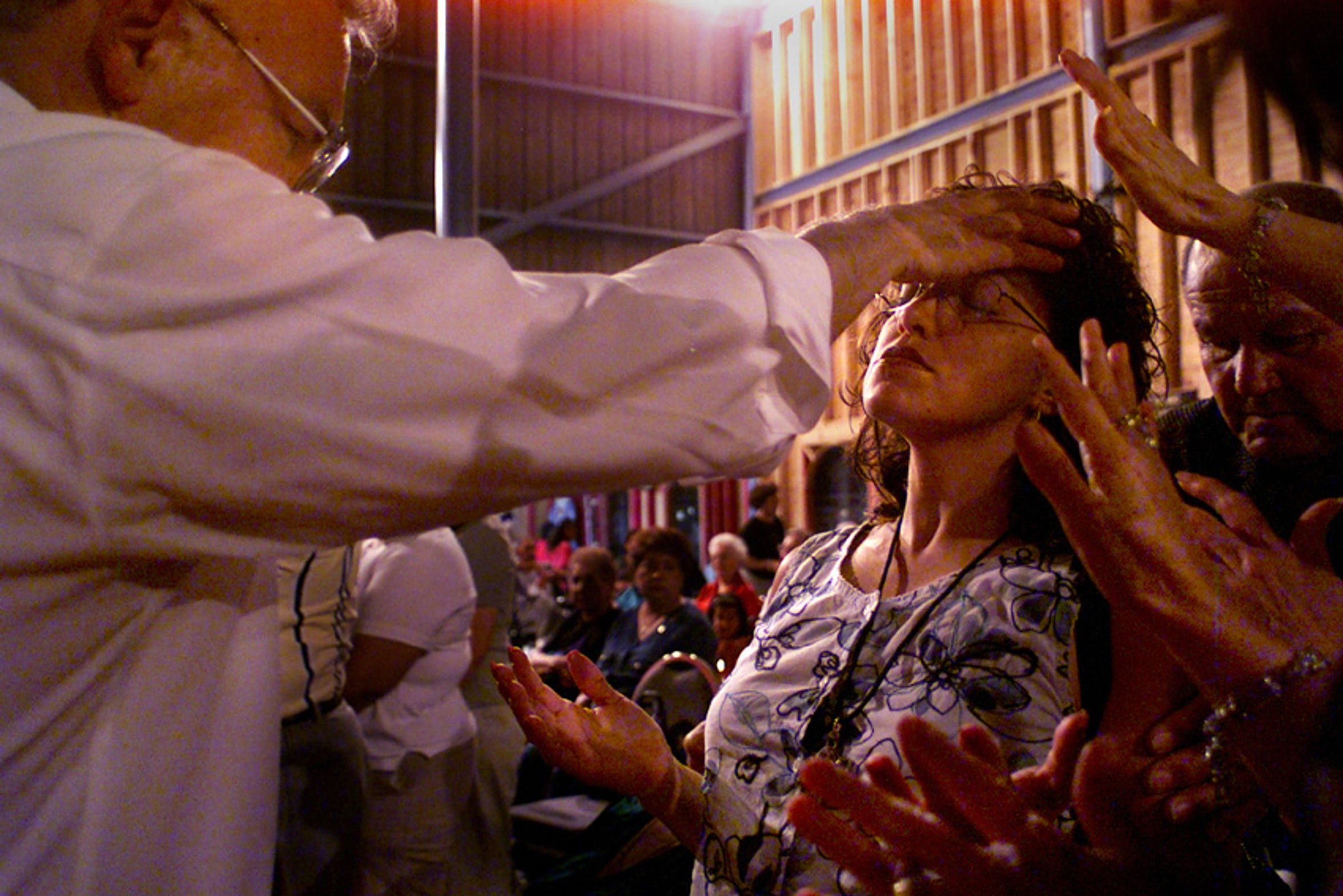 Albert Huerta (left), tries to heal Esperanza Anderson, of Corpus Christi, as others add their support during a revival meeting at Our Father's House, formerly the Texas Sky Amphithearter, on Tuesday, June 25, 2002. Huerta believes the Holy Spirit and God speak through him, and with their grace he can heal people who are physically sick.