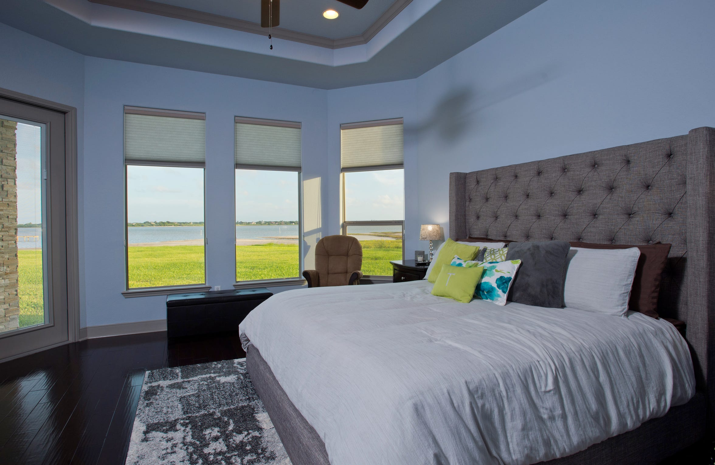 The large yet cozy master bedroom takes in Oso Bay water views from a wall of windows