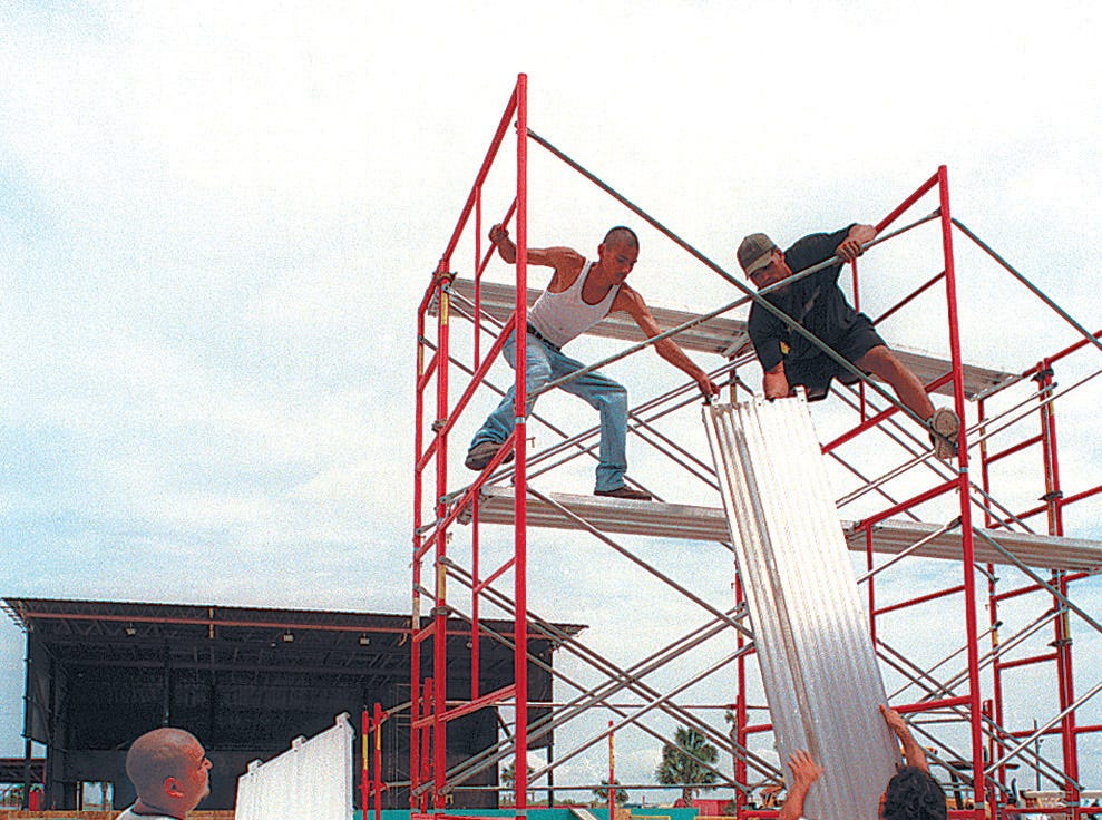 Workers at Texas Sky Festival Park prepare a 15-foot high scaffolding on July 31, 1997 to hold spot lights for Sunday's Lollapalooza show.