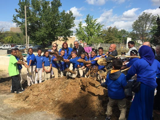 Cooper's Ferry CEO Kris Kolluri, Camden Mayor Frank Moran and Councilwoman Sheila Davis (left to right) help students from KIPP Cooper Norcross School break ground on a park rehab project at 4th and Clinton streets.