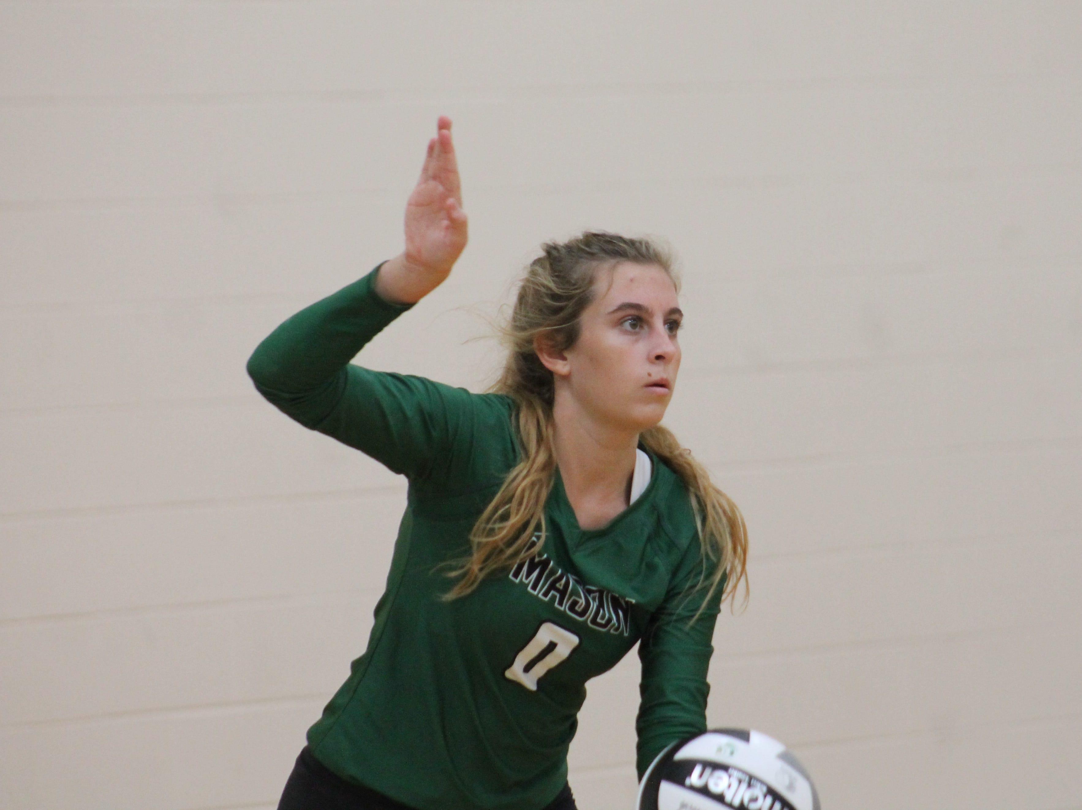 Junior libero Sophia Hoffman prepares to send the ball over the net for Mason