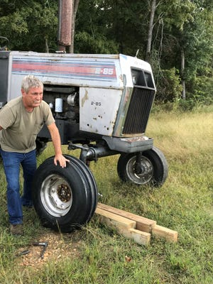 Stan Hembree works on his tractor in Woodlawn. He found a sleeping bag and blankets on his property earlier Wednesday, and authorities said it's one of their best leads yet in the search for Kirby Wallace.