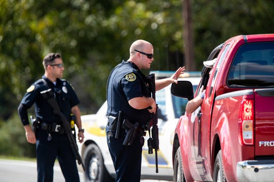 Police guard a roadblock on Lylewood Road at Cooper Creek and York Landing Roads during a manhunt for an accused murderer Wednesday, Oct. 3, 2018, in Woodlawn, Tenn.