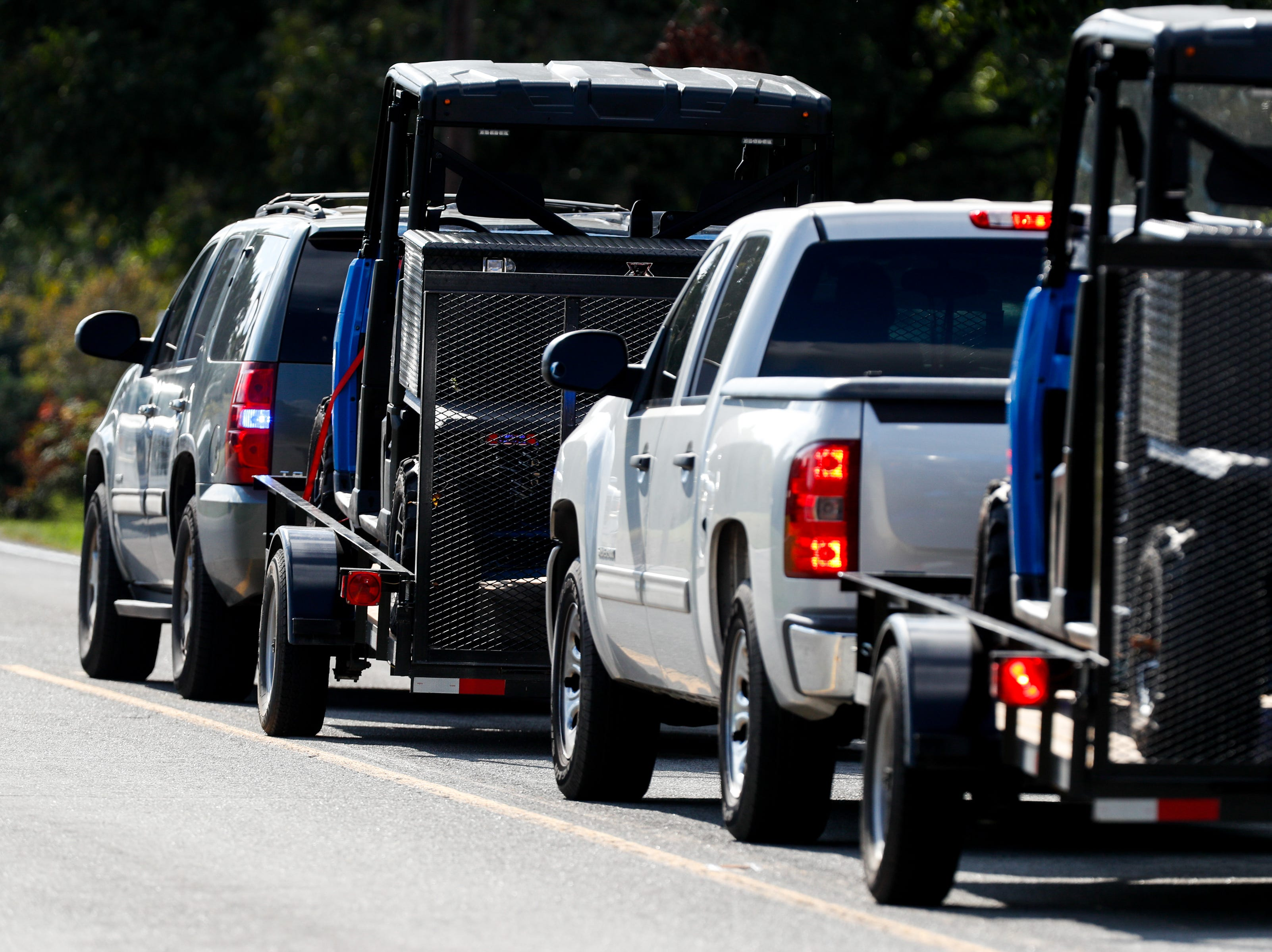 Police take off road vehicles past the roadblock on Lylewood Road at Cooper Creek and York Landing Roads during a manhunt for an accused murderer Wednesday, Oct. 3, 2018, in Woodlawn, Tenn.