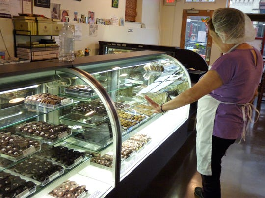 Carol Freedman, co-owner of Carol's Creative Chocolatez in Somerville, looking at her creations through her glass countertop display.