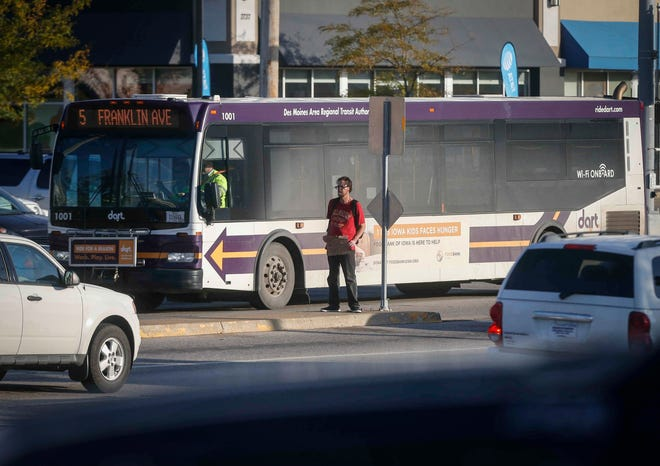 A panhandler begs motorists for spare change from Merle Hay as a DART bus passes through the intersection in Des Moines on Wednesday, Oct. 3, 2018.