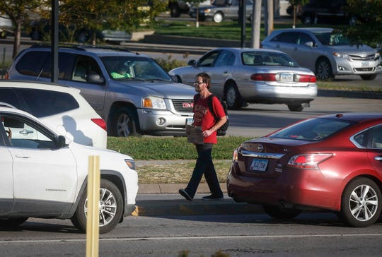 A panhandler solicits money from passing motorists Oc.t 3 at the intersection of Merle Hay and Douglas Avenue in Des Moines.