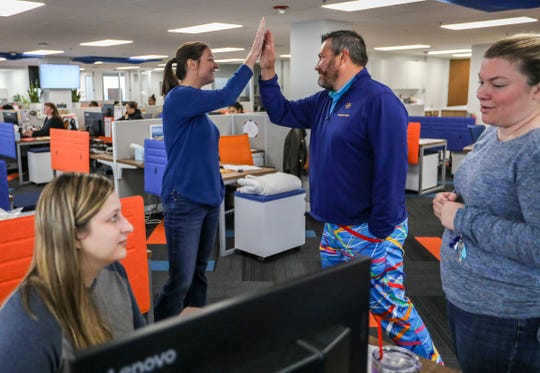 Chris Tillotson, president, center right, high fives Kelly Kondratko, therapy supervisor, while Katie Kilbourn,executive coordinator, left, and Angie Langford, director of therapy, look on at Custom Home Health & Custom Hospice, a Detroit Free Press Top Workplace, in their new offices in Troy, Mich. on Tuesday, Oct. 2, 2018.
