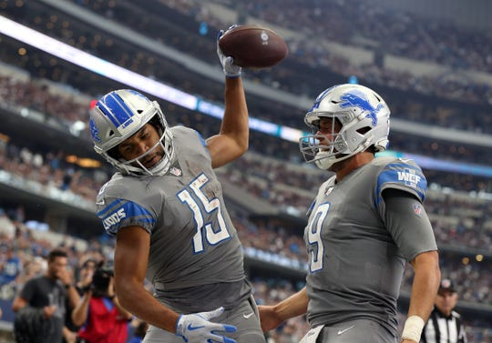 Golden Tate spikes the ball while celebrating his fourth-quarter touchdown Sunday with Matthew Stafford.