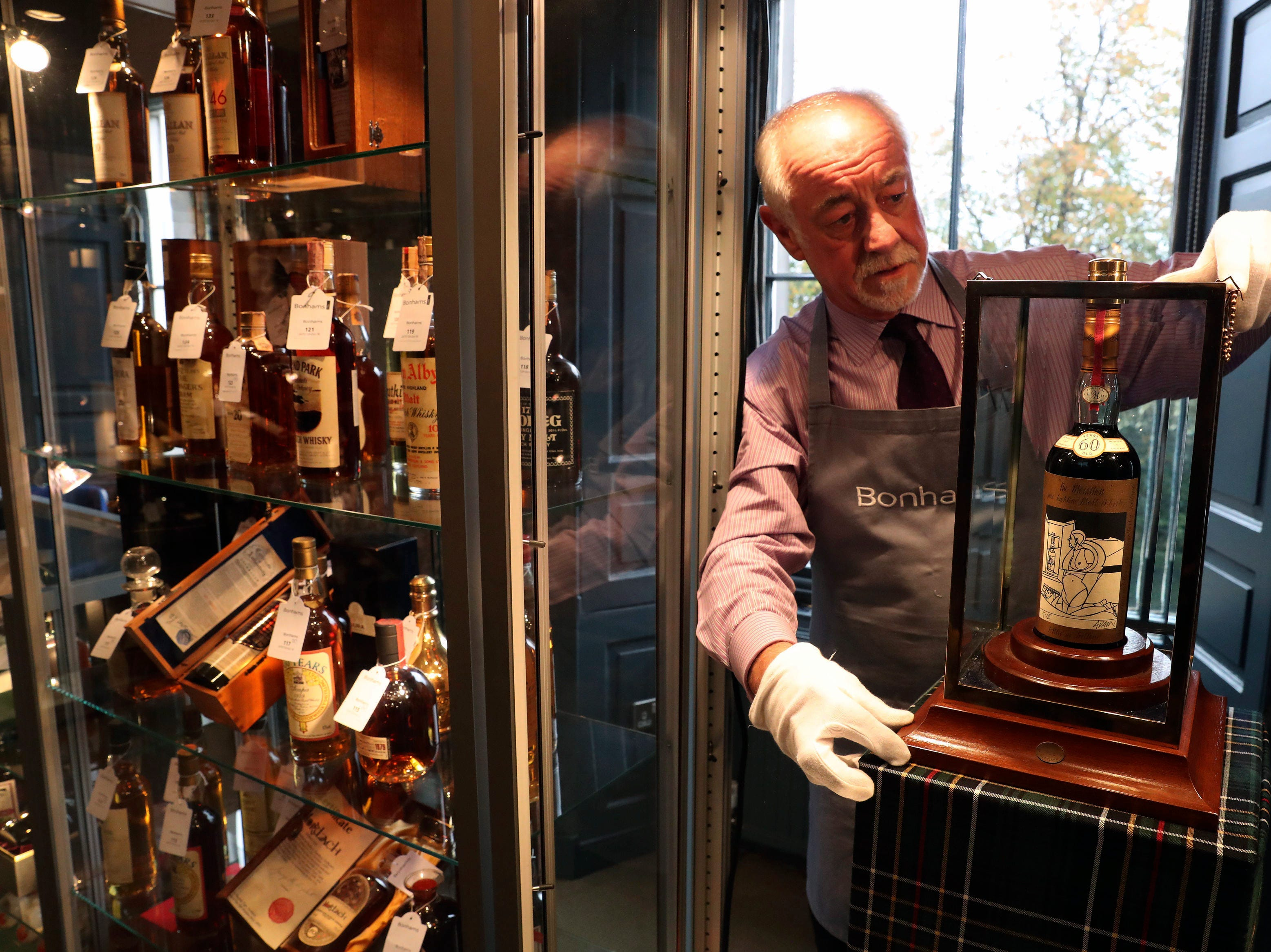 Danny McIlwraith from Bonhams auction house holds bottle of the world's rarest and most valuable whisky, The Macallan Valerio Adami, at the Bonhams Whisky Sale at their Edinburgh auction house in Edinburgh, Wednesday, Oct. 3, 2018. It was eventually sold for £848,750 ($1,102,516).