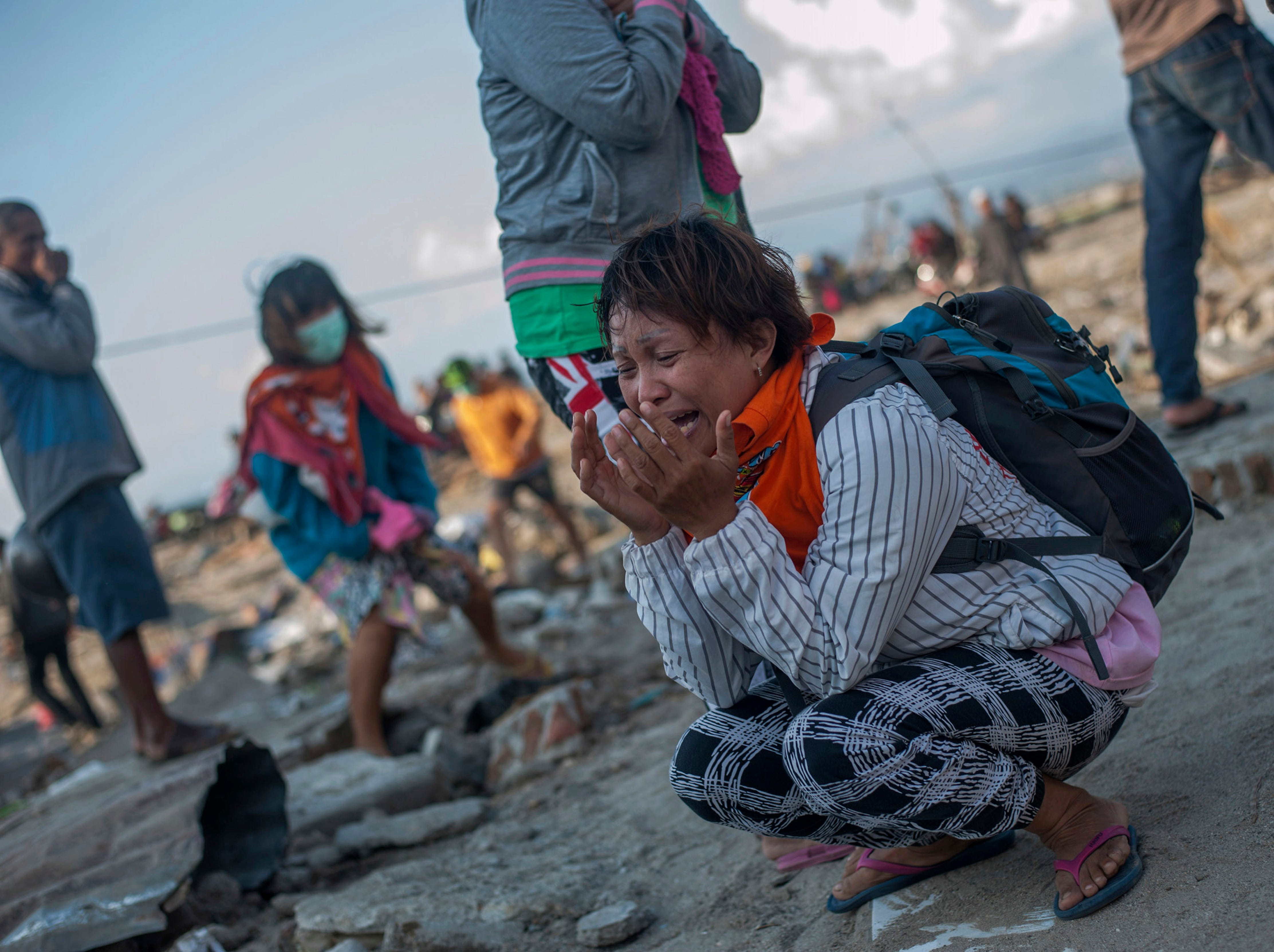 Residents react as rescuers recover the body of a tsunami victim in Palu, Central Sulawesi, Indonesia, Wednesday, Oct. 3, 2018.