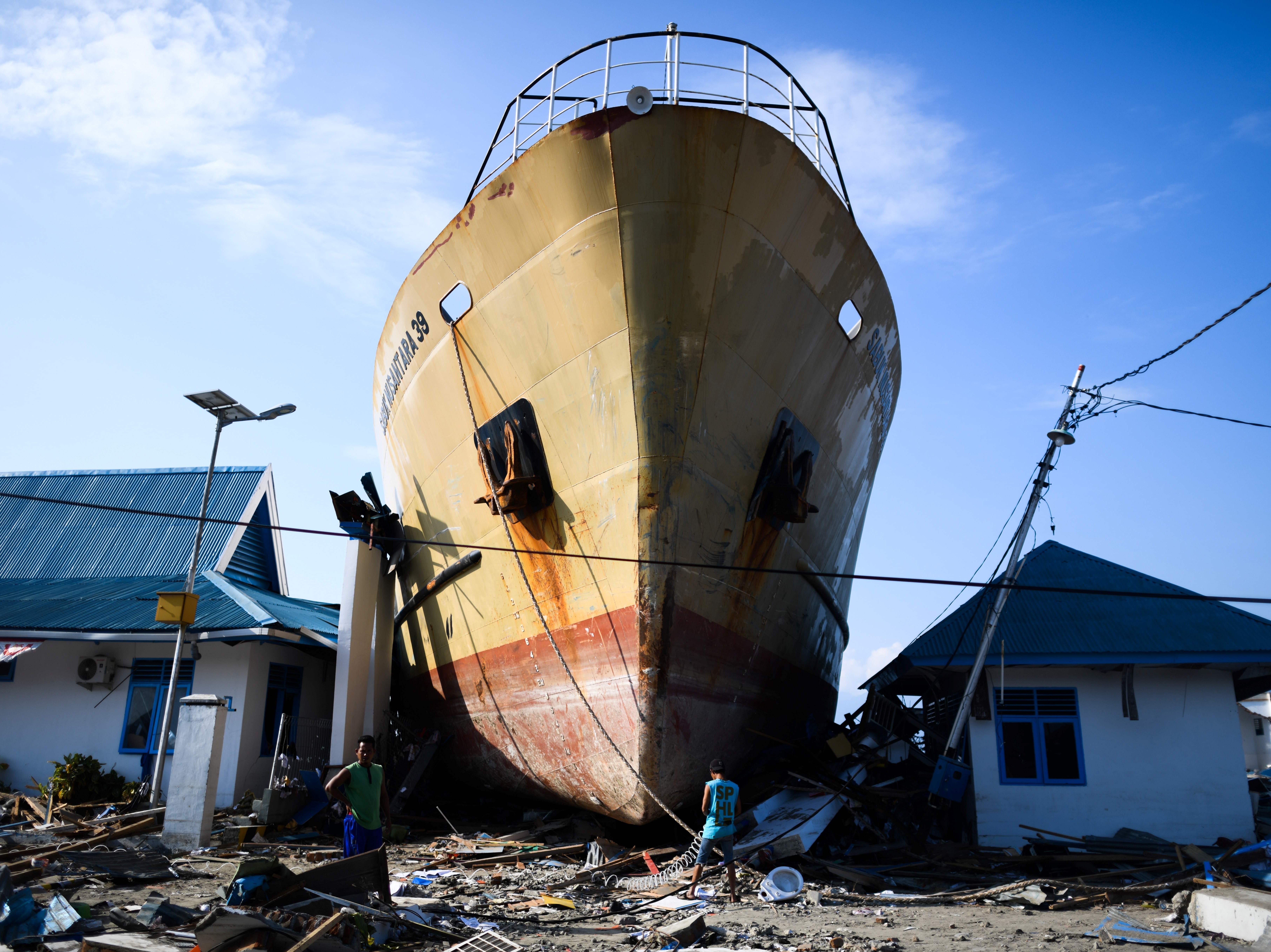 Quake survivors make their way past a passenger ferry wasehd up in Wani, Central Sulawesi, Indonesia, on October 3, 2018, after an earthquake and tsunami hit the area on September 28.