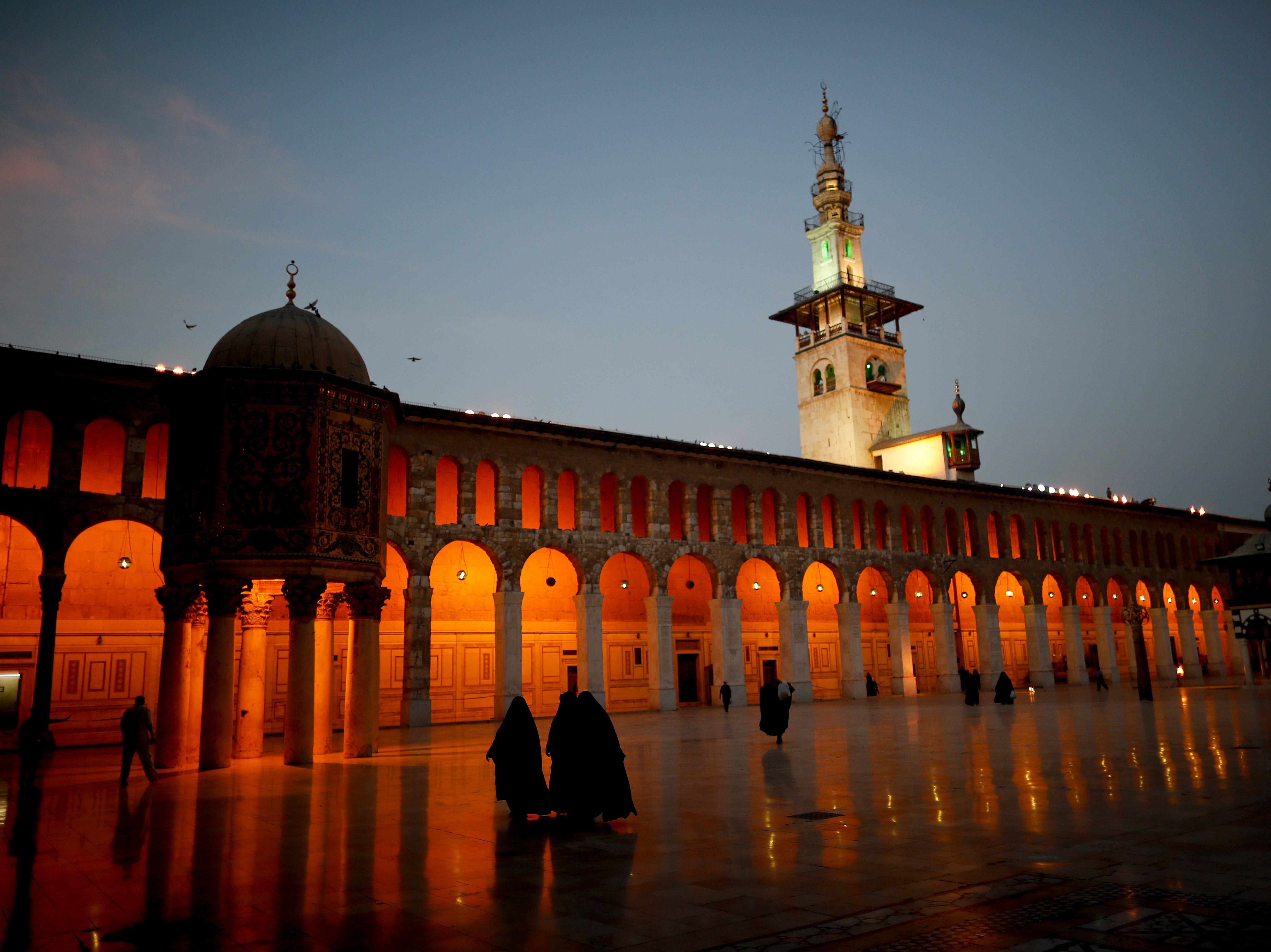 """Muslim women walk in the courtyard of the 7th century Umayyad Mosque in Damascus, Syria, Wednesday, Oct. 3, 2018. President Bashar Assad told a little-known Kuwaiti newspaper Wednesday that Syria has reached a """"major understanding"""" with Arab states after years of hostility over the country's civil war."""