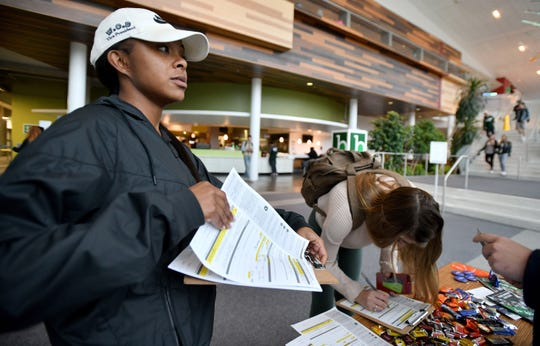 Members of NextGen America, Shanel Thomas (Black top and white hat) and Jenna Chapman (horizontal striped top) try to get MSU students to register or move their registration to East Lansing in Brody Hall on MSU's campus.