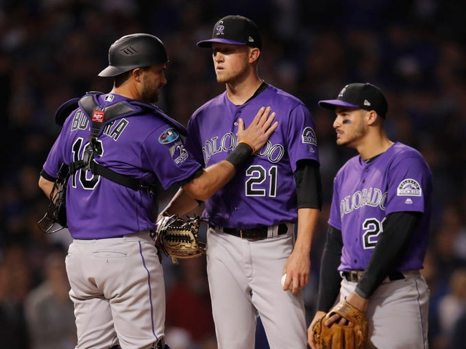 Oct 2, 2018; Chicago, IL, USA; Colorado Rockies starting pitcher Kyle Freeland (21) is greeted catcher Drew Butera (16) as Freeland waits to be relieved in the 7th inning against the Chicago Cubs in the 2018 National League wild card playoff baseball game at Wrigley Field.