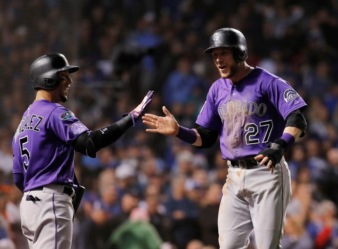 Oct 2, 2018; Chicago, IL, USA; Colorado Rockies shortstop Trevor Story (27) celebrates with teammate Carlos Gonzalez (5) after scoring a run against the Chicago Cubs in the 13th inning in the 2018 National League wild card playoff baseball game at Wrigley Field. Mandatory Credit: Jim Young-USA TODAY Sports