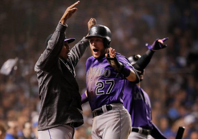 Oct 2, 2018; Chicago, IL, USA; Colorado Rockies shortstop Trevor Story (27) celebrates with teammates after scoring a run against the Chicago Cubs in the 13th inning in the 2018 National League wild card playoff baseball game at Wrigley Field. Mandatory Credit: Jim Young-USA TODAY Sports