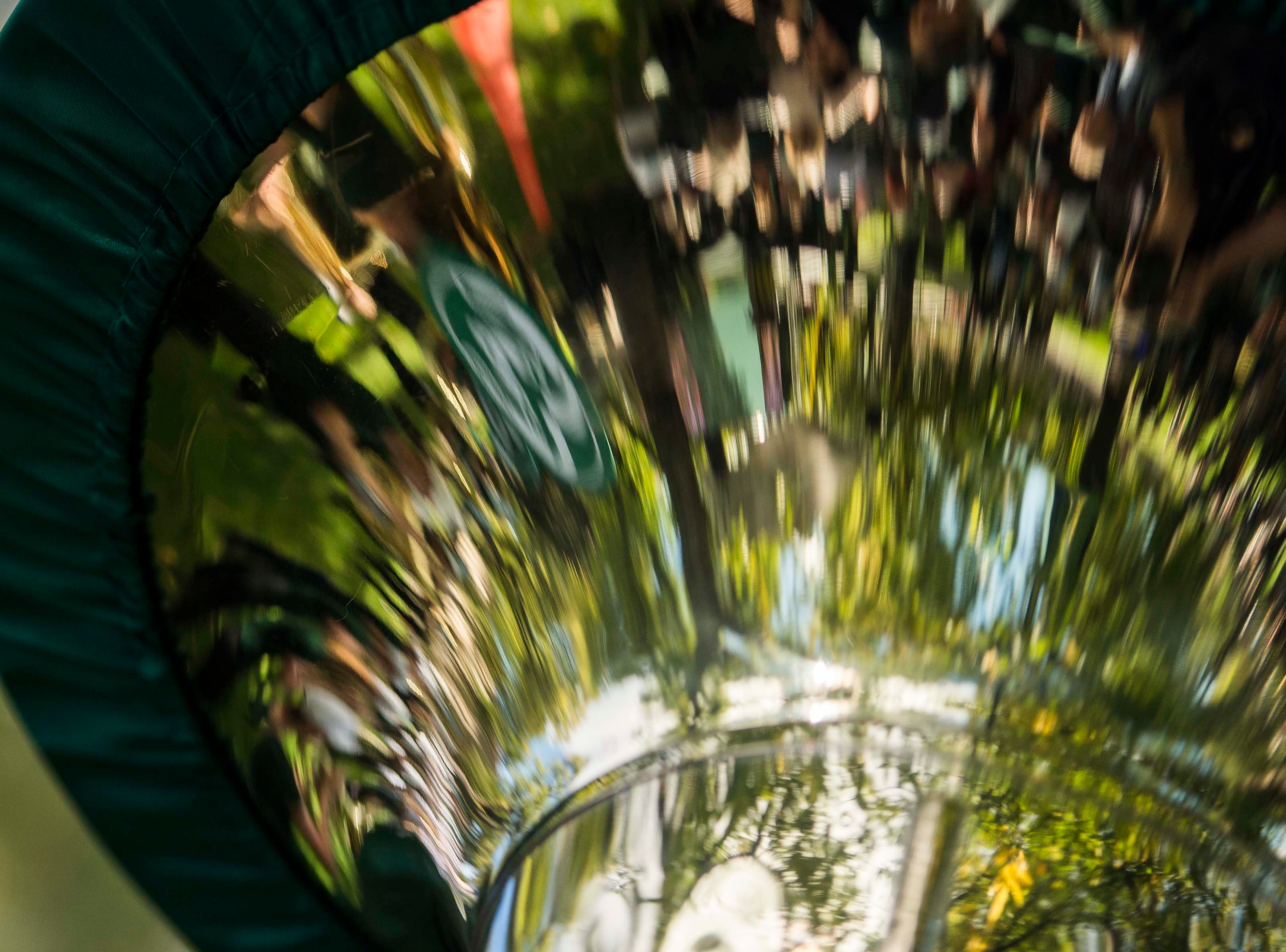 The CSU marching band is reflected in a tuba on Wednesday, Oct. 3, 2018, during the 2018 fall address at the Colorado State University campus in Fort Collins, Colo.