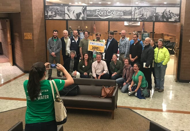 Council member Ross Cunniff, top row center, poses with supporters of 100 percent renewable electricity by 2030 after a vote in support of that resolution on Tuesday, Oct. 2, 2018.
