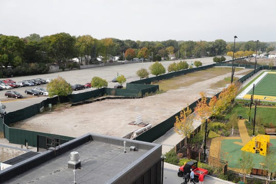 The Green Bay Packers plan to build townhouses and apartments in the enclosed area and the parking lot in the distance, seen looking southwest from top of Ariens hill in the Titletown District