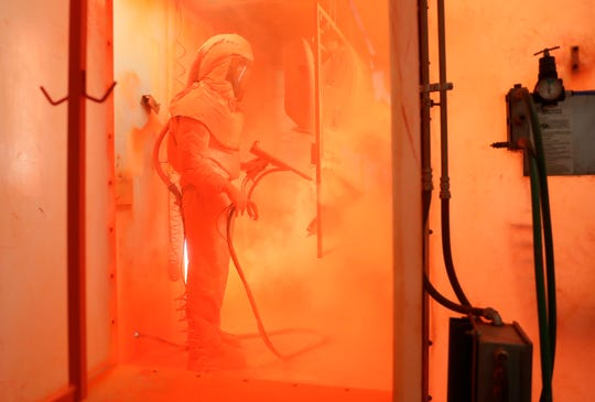 Ariens Co. employee Jacob Novak paints orange Sno-Thro parts Monday at the production facility in Brillion.