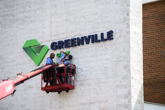 Workers install a new sign at the Greenville Convention Center on Wednesday, Oct. 3, 2018.