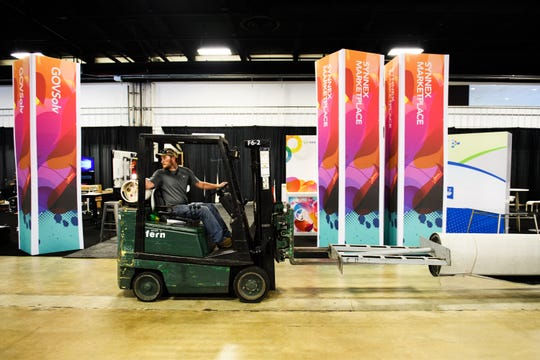 A worker uses a forklift to transport carpeting during setup of the SYNNEX Inspire Conference at the Greenville Convention Center on Wednesday, Oct. 3, 2018.