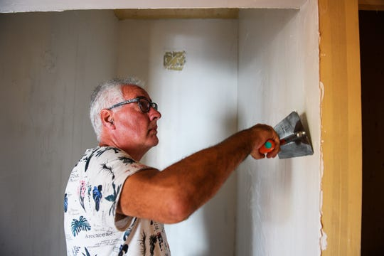 Konrad Lentschig applies stucco on a wall of his home in the Sterling neighborhood of Greenville.