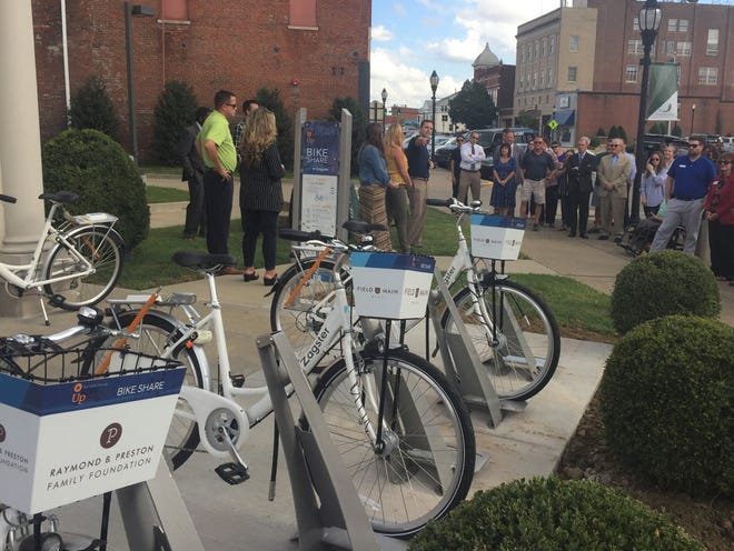 Will Monsour makes a point during Wednesday's ribbon-cutting for a local bike share program. He, Courtney Vowels and Abbey Dixon (both standing with Monsour) came up with the idea while they were taking part in the Henderson Leadership Initiative.