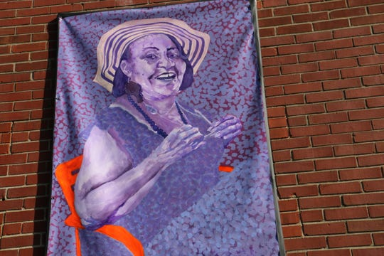 """A portrait of Terri Taylor, part of the """"Greatriarchs of Monon 16"""" series, hangs on a building on east 16th Street."""