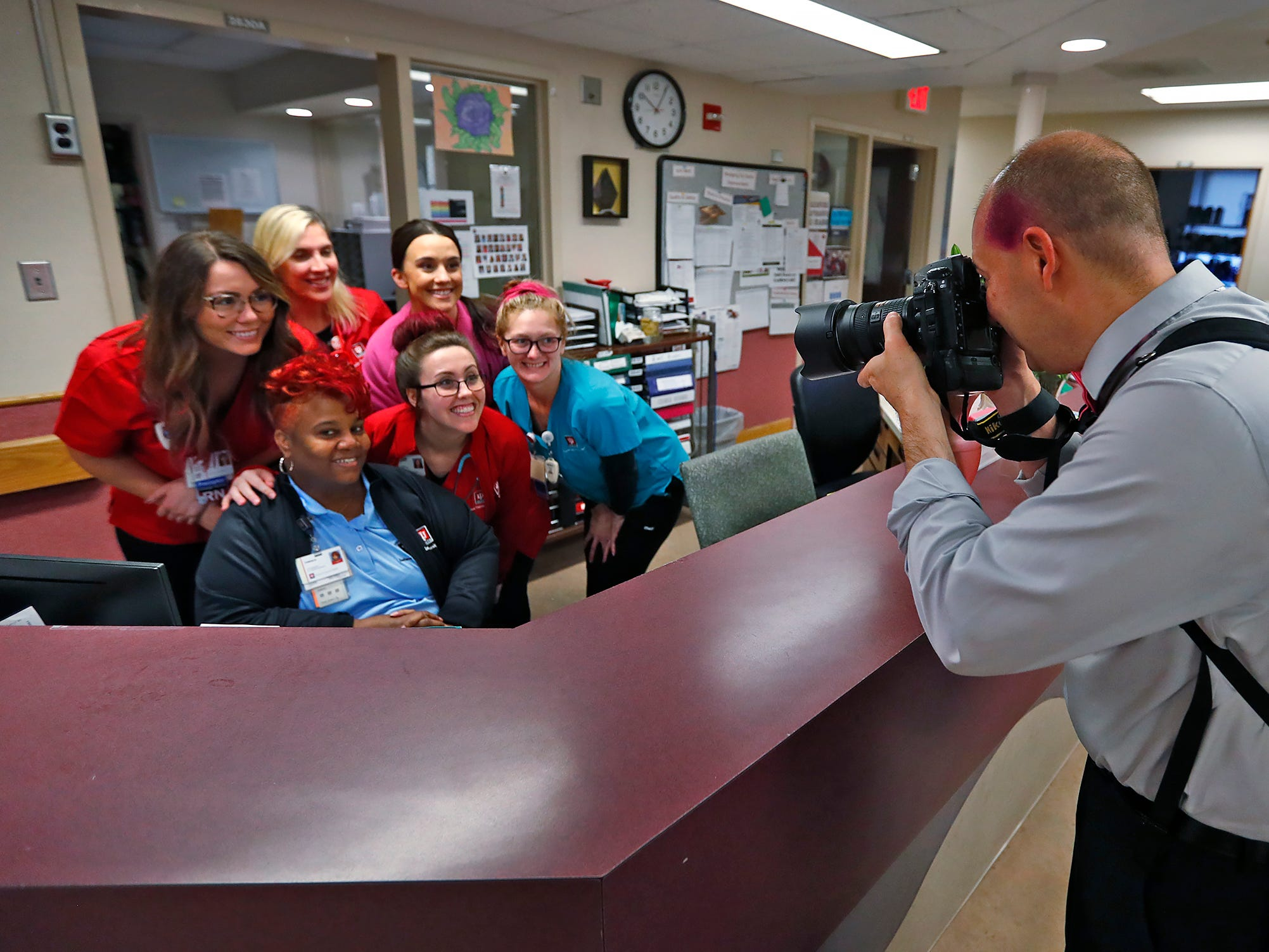 "IU Health photographer Mike Dickbernd, right, takes a photo of pink-haired and pink-highlighted staff at the Indiana University Melvin and Bren Simon Cancer Center, Wednesday, Oct. 3, 2018.  The visual journalist even has a spot of pink in his hair.  IU Health staff members are given the opportunity to ""go pink"" to show support for their patients as part of Breast Cancer Awareness month."