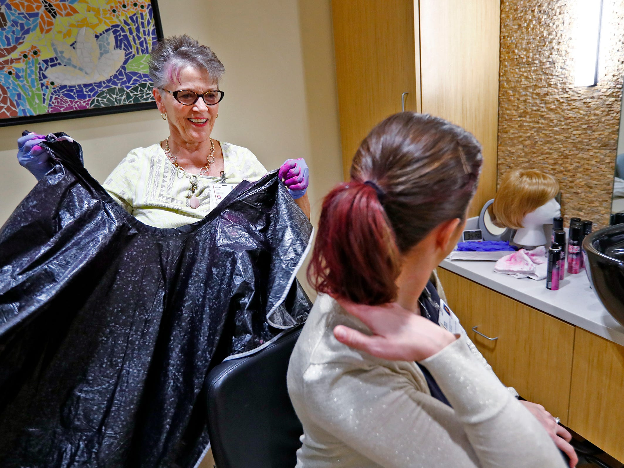 "Wilma Cross smiles as she sees her pink handiwork, after spraying pink into Beth Resner's hair, at the Wig Bank in the Indiana University Melvin and Bren Simon Cancer Center, Wednesday, Oct. 3, 2018.  IU Health staff members are given the opportunity to ""go pink"" to show support for their patients as part of Breast Cancer Awareness month."