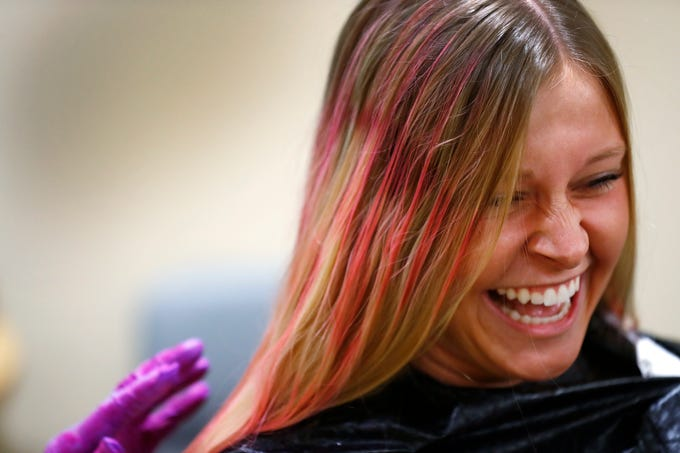 "Kati Dendler laughs as she gets her hair spray painted pink by Wilma Cross at the Wig Bank in the Indiana University Melvin and Bren Simon Cancer Center, Wednesday, Oct. 3, 2018.  IU Health staff members are given the opportunity to ""go pink"" to show support for their patients as part of Breast Cancer Awareness month."