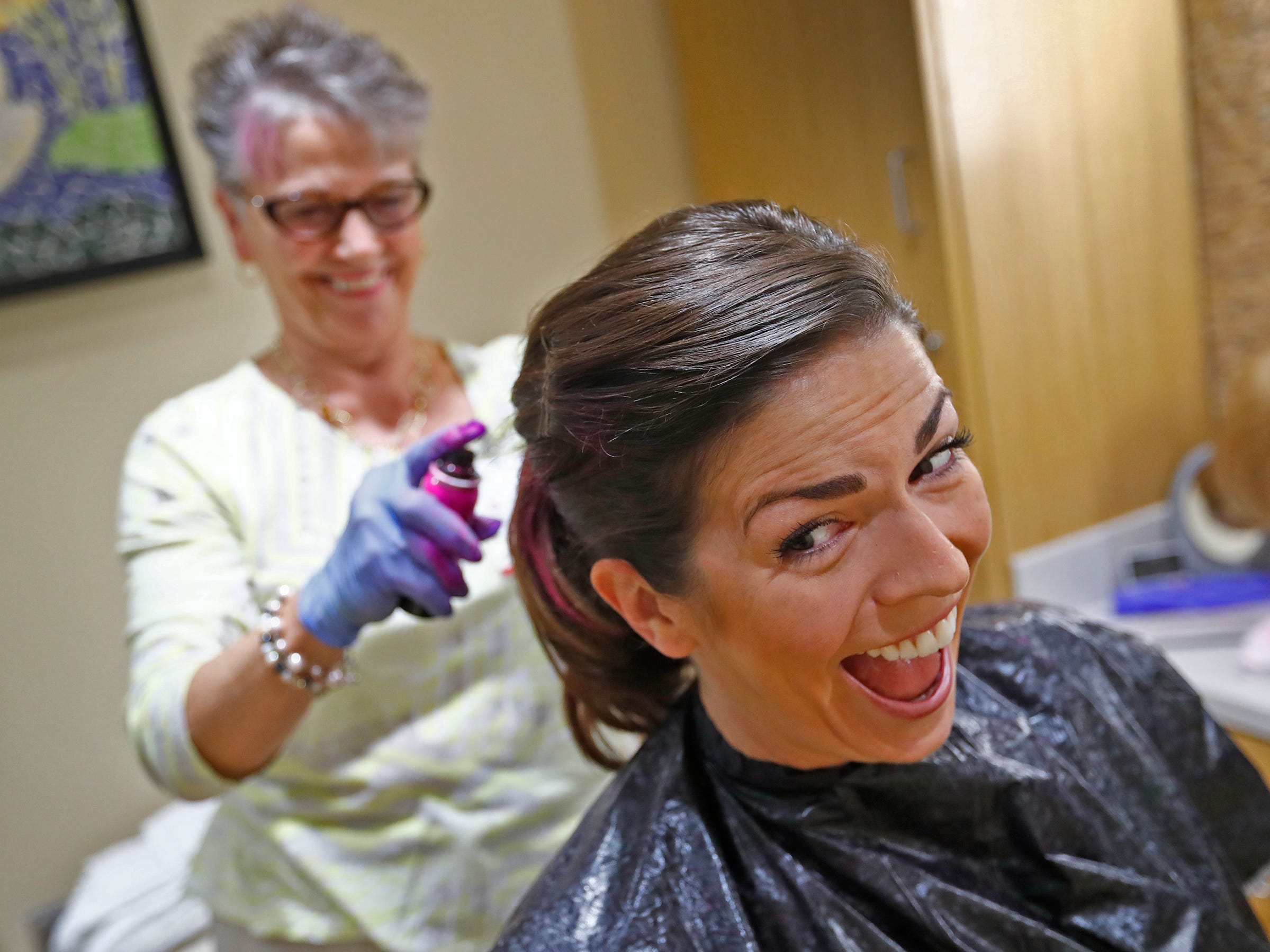 "Wilma Cross, left, sprays pink into an exhilarated Beth Resner's hair at the Wig Bank in the Indiana University Melvin and Bren Simon Cancer Center, Wednesday, Oct. 3, 2018.  IU Health staff members are given the opportunity to ""go pink"" to show support for their patients as part of Breast Cancer Awareness month."