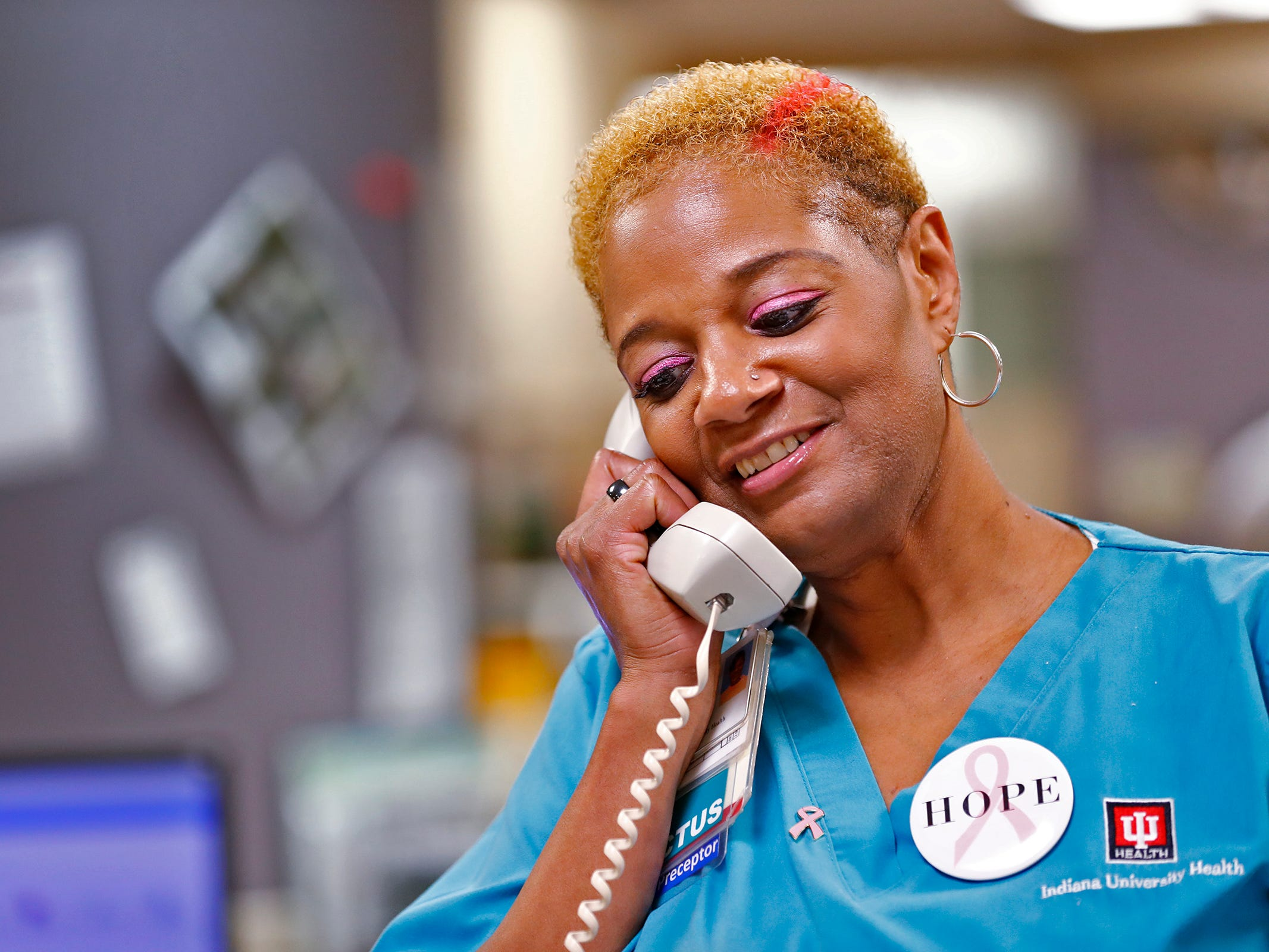"Crystal Crayton takes a call as she sports a streak of pink in her hair and pink eye shadow at the Indiana University Melvin and Bren Simon Cancer Center, Wednesday, Oct. 3, 2018.  IU Health staff members are given the opportunity to ""go pink"" to show support for their patients as part of Breast Cancer Awareness month."