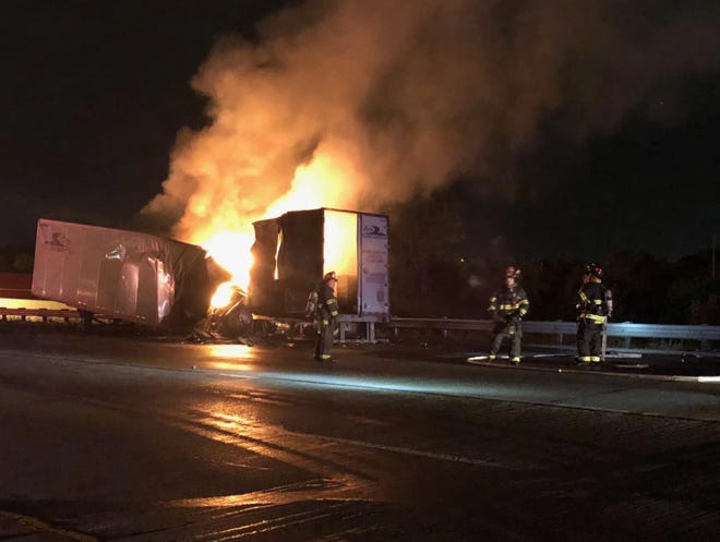 Firefighters work to extinguish a fire caused by an explosion inside a semi-truck's trailer. The fire shut down eastbound Interstate 70 on Indianapolis' east side for about two hours early Wednesday morning.