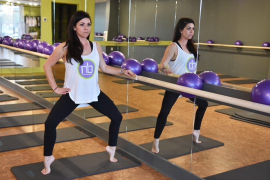 Tabatha Smith, owner of Neighborhood Barre Powell, demonstrates a workout technique at the bar.